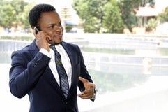 非裔美国人的商人谈话与电话 免版税图库摄影