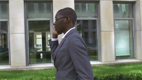 非裔美国人的商人谈话在手机,站立在他的办公室前面 慢的行动