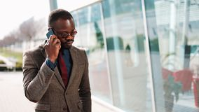 非裔美国人的商人谈话在站立近的办公室中心的一个巧妙的电话 事务,人们,通信 影视素材