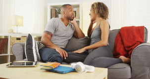 非裔美国人的夫妇一起谈话在长沙发 免版税库存图片
