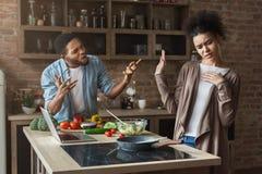 非裔美国人的夫妇烹调和争吵在顶楼厨房里 免版税图库摄影