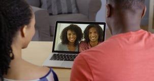 非裔美国人的夫妇谈话与在膝上型计算机的家庭 免版税库存照片