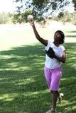 年轻非裔美国人的女子投掷的棒球公园 图库摄影