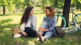 非裔美国人的女孩与她的白种人朋友谈话坐草坪在公园,现代自行车,并且背包是可看见的 影视素材
