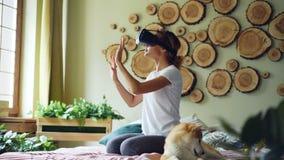 非裔美国人的女孩使用虚拟现实玻璃在家坐床,她移动手和头和微笑 股票录像