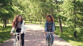 非裔美国人的女孩在有她的白种人朋友的城市公园骑自行车,少妇谈话并且笑 影视素材
