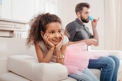 非裔美国人的女孩坐喝从玩具杯子的沙发和父亲 免版税库存照片