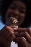 非裔美国人的女孩画象有一朵花的在她的手上 免版税库存照片