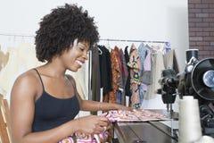 非裔美国人的女性在缝纫机的裁缝缝的布料 免版税图库摄影