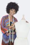 非裔美国人的女性时装设计师画象有裁缝的钝汉的在灰色背景 免版税库存照片