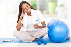 非裔美国人的妇女休息的健身房 图库摄影