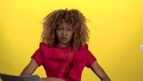 非裔美国人的妇女在她的手上拿着纸片并且丢掉他们 黄色背景 慢的行动 股票视频