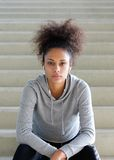 年轻非裔美国人的妇女坐与耳机的步 库存照片