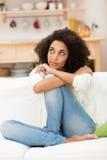 年轻非裔美国人的妇女坐的作白日梦 库存照片