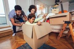 非裔美国人的家庭、父母和女儿,打开箱子和搬入一个新的家 库存图片