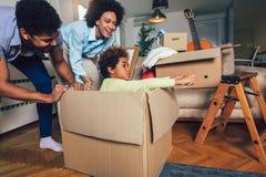 非裔美国人的家庭、父母和女儿,打开箱子和搬入一个新的家 免版税库存图片