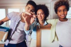非裔美国人的家庭搬入一栋新的公寓,他们在他们的手保留从公寓的钥匙并且看 免版税图库摄影