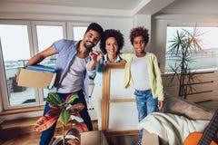 非裔美国人的家庭搬入一栋新的公寓,他们在他们的手保留从公寓的钥匙并且看 免版税库存照片