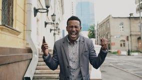 非裔美国人的快乐的商人愉快在谈关于他新的事业的电话以后 免版税库存照片