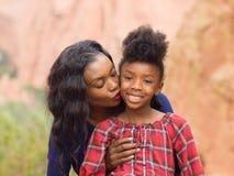 非裔美国人的母亲亲吻她的孩子 免版税库存图片