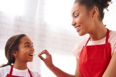 非裔美国人的母亲喂养小女儿 免版税图库摄影