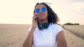 非裔美国人的混合的族种少年谈话在她的手机佩带的太阳镜在日落 影视素材