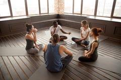 非裔美国人的瑜伽辅导员谈话与不同的小组sittin 免版税库存照片