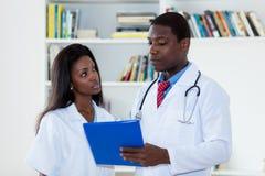 非裔美国人的男性医生谈话与关于患者的护士 库存图片