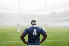 非裔美国人的男性橄榄球球员身分用在臀部的手在体育场内 库存照片