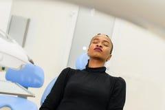 非裔美国人的种族黑人在等待她的牙医的牙齿椅子的患者坐的闭合值的眼睛 免版税库存照片