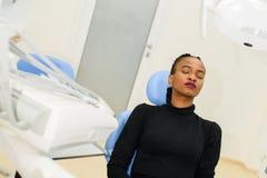 非裔美国人的种族黑人在等待她的牙医的牙齿椅子的患者坐的闭合值的眼睛 免版税库存图片