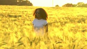 非裔美国人的戴一副白色T恤杉和蓝色飞行员太阳镜的女孩少年少妇走在一块麦田 影视素材