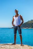 非洲黑人佩带的白色背心和蓝色短的牛仔裤 免版税库存图片