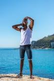 非洲黑人佩带的白色背心和蓝色短的牛仔裤 免版税库存照片