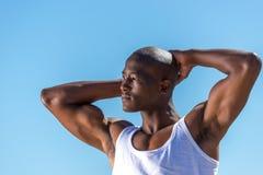 非洲黑人佩带的白色背心和蓝色短的牛仔裤 免版税图库摄影