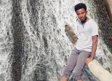 年轻非洲人坐在河瀑布的树干 免版税库存图片