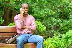 非洲人坐长凳,谈话在电话 免版税库存图片