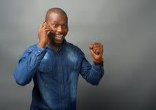 非洲人激动,接到在一个手机的一个电话 免版税图库摄影