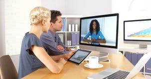 非洲企业同事谈话与她的在互联网的队友 免版税库存照片