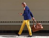 年轻非洲商人走的Wirth袋子和手机 免版税库存照片