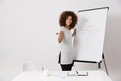 非洲在白色背景的女孩微笑的常设近的标志whiteboard 库存照片