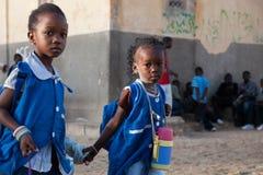 非洲女孩在途中的蓝色穿戴了到学校在塞内加尔 免版税库存照片