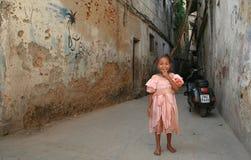 非洲女孩微笑,站立在庭院里毁坏了石头 图库摄影