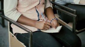 非洲女性手特写镜头视图  坐椅子和写在笔记本的妇女 演讲的学生女孩