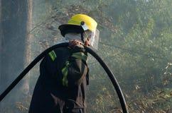 非洲女性消防队员被帮助熄灭灌木草原火涉嫌通过短缺输电线在希尔顿, Pietermaritzbu开始了 免版税图库摄影