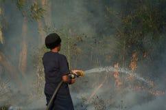 非洲女性消防队员被帮助熄灭灌木草原火涉嫌通过短缺输电线在希尔顿, Pietermaritzbu开始了 免版税库存图片