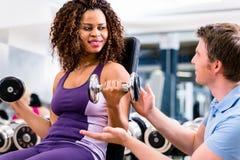 非洲妇女和教练员在锻炼在健身房 免版税图库摄影