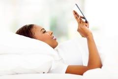 非洲妇女在使用片剂的床上 免版税库存照片