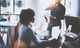 非洲妇女握纸手和谈话与伙伴 做巨大企业讨论的工友年轻队  图库摄影
