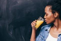 非洲妇女饮料橙汁 健康寿命 免版税图库摄影